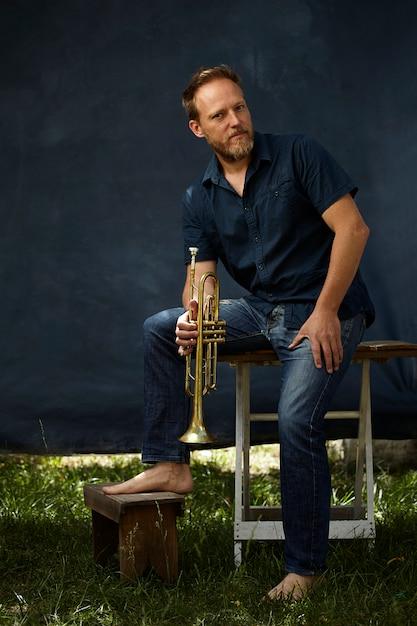 Musiker posiert mit seinem instrument Kostenlose Fotos