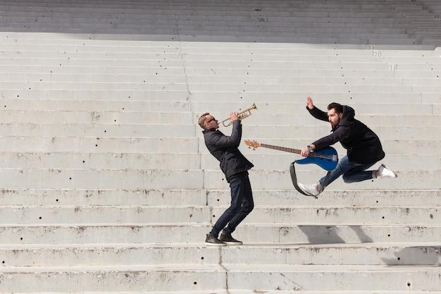 Musiker spielen und springen Kostenlose Fotos