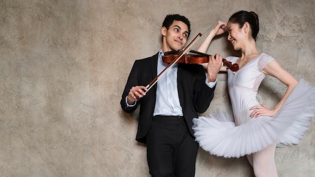 Musiker spielt geige und ballerina und hört zu Kostenlose Fotos