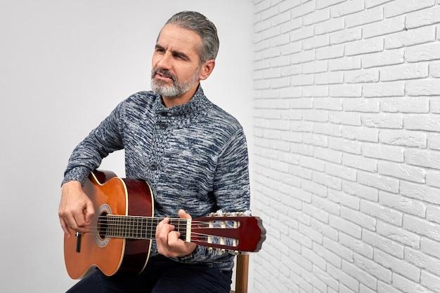 Musiker spielt gitarre und singt. Premium Fotos