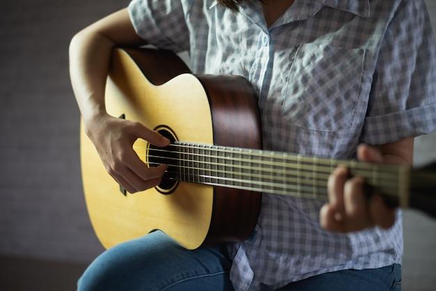 Musikermädchen, das akustikgitarre spielt Premium Fotos