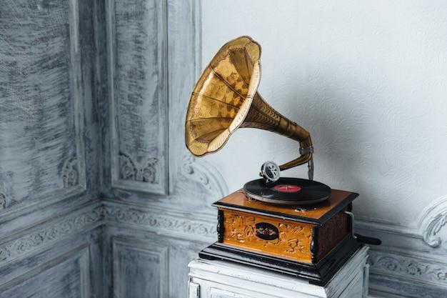 Musikgerät. altes grammophon mit platte oder vinylscheibe auf holzkiste. antiker plattenspieler aus messing Premium Fotos