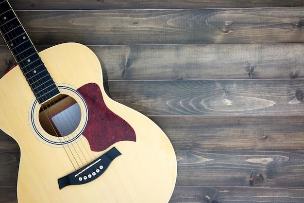 Musikinstrumentgitarre auf altem hölzernem hintergrund mit kopienraum. vintage-effekt. Premium Fotos