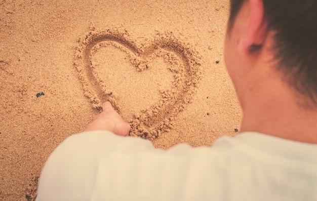 Muskel Mann zeichnen Herz auf Sand. Internationales Sonnenlicht und ...