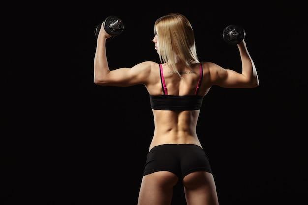 Muskulöse frau auf seinem rücken heben von gewichten auf einem schwarzen hintergrund Kostenlose Fotos