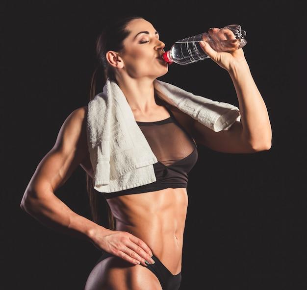 Muskulöse frau in trinkwasser der schwarzen unterwäsche Premium Fotos