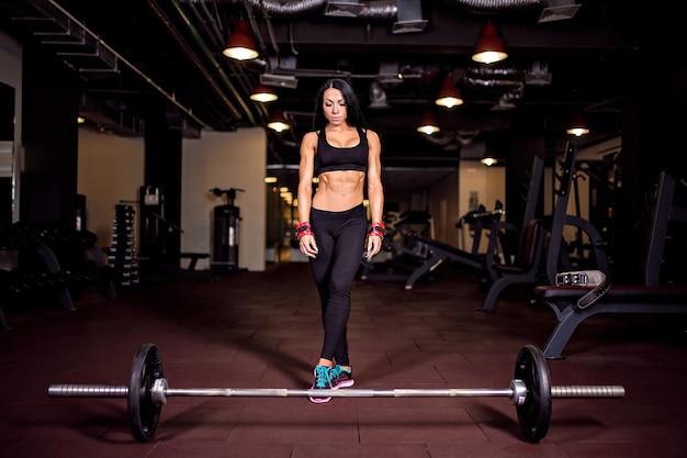 Muskulöse junge eignungsfrau, die für schwere kreuzhebenübung sich vorbereitet Premium Fotos