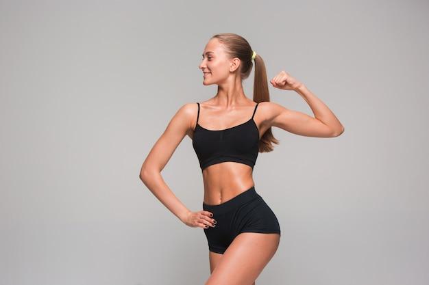Muskulöse junge sportlerin auf grau Kostenlose Fotos