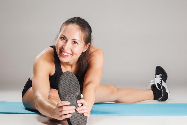 Muskulöse junge sportlerin, die auf grau ausdehnt Kostenlose Fotos