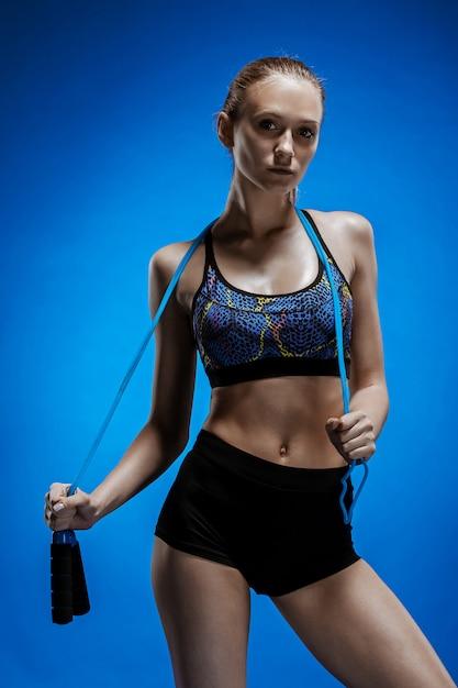 Muskulöse junge sportlerin mit einem springseil auf blau Kostenlose Fotos