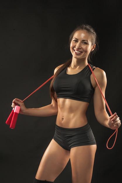 Muskulöse junge sportlerin mit einem springseil auf schwarz Kostenlose Fotos