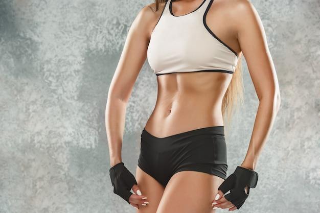 Muskulöse junge sportlerin posiert Kostenlose Fotos