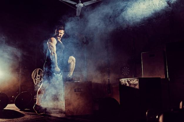 Muskulöser attraktiver kaukasischer bärtiger mann, der zwei kettlebells in einer turnhalle anhebt. hantelscheiben, hantel und reifen im hintergrund. Premium Fotos