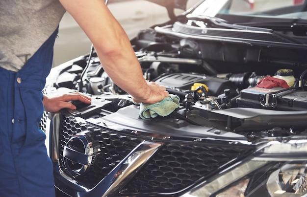Muskulöser autoservice-arbeiter, der fahrzeug repariert. Kostenlose Fotos