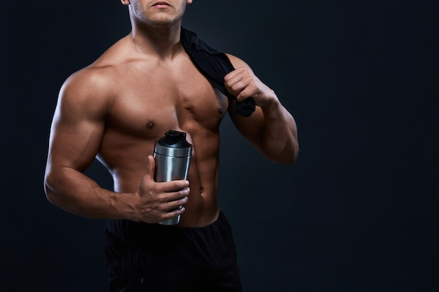 Muskulöser bodybuilder mit schüttel-apparatflasche auf schwarzem starker athletischer mann zeigt körper, bauchmuskeln, brustmuskeln, bizeps und trizeps heraus arbeiten und zunehmen gewicht. bodybuilding. Premium Fotos