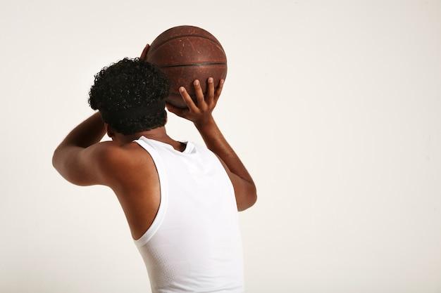 Muskulöser dunkelhäutiger athlet mit einem afro und einem stirnband, die ein weißes ärmelloses hemd tragen und einen alten braunen lederbasketball auf weiß werfen Kostenlose Fotos