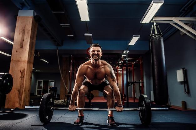 Muskulöser eignungsmann, der kreuzheben ein barbell in der modernen eignungsmitte tut. funktionstraining. Premium Fotos