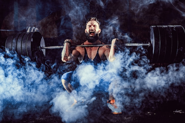 Muskulöser eignungsmann, der kreuzheben ein barbell über seinem kopf in der modernen eignungsmitte tut. funktionstraining. Premium Fotos