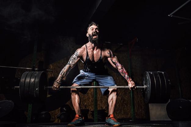 Muskulöser eignungsmann, der kreuzheben eines barbell in der modernen eignungsmitte tut. funktionstraining. Premium Fotos