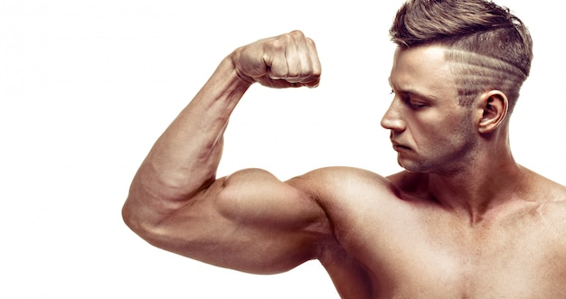 Muskulöser gutaussehender mann, der auf weißem hintergrund aufwirft. zeigt seinen bizeps. Premium Fotos