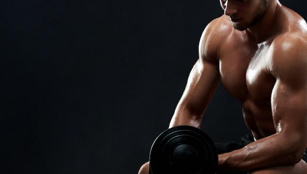 Muskulöser junger mann, der gewichte auf schwarzem hintergrund anhebt Kostenlose Fotos