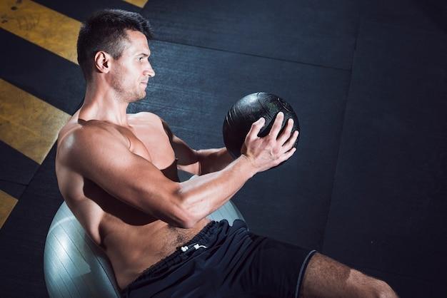 Muskulöser junger mann, der mit medizinball trainiert Kostenlose Fotos