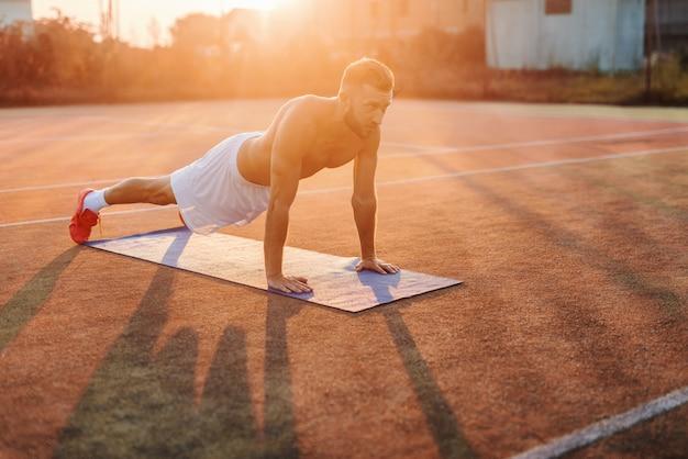 Muskulöser kaukasischer mann, der morgens im sommer liegestütze auf dem platz macht. Premium Fotos
