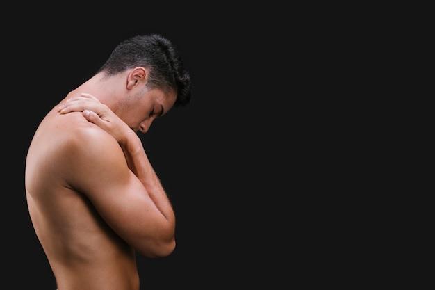 Muskulöser kerl, der schulter reibt Kostenlose Fotos