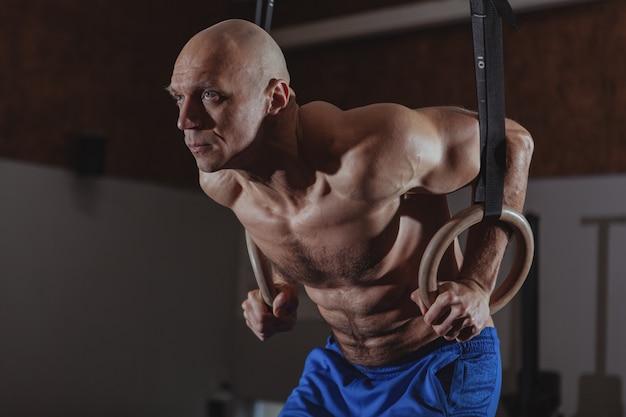 Muskulöser männlicher crossfit athlet, der auf gymnastischen ringen ausarbeitet Premium Fotos