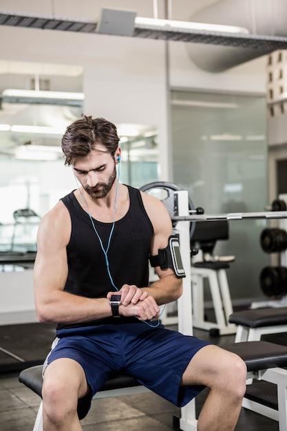 Muskulöser mann, der auf barbellbank sitzt und smartwatch an der turnhalle verwendet Premium Fotos