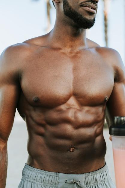 Muskulöser mann, der einen proteindrink trinkt Premium Fotos