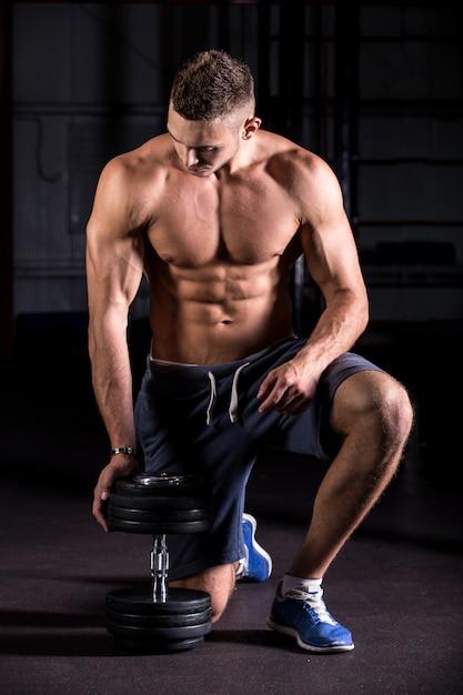 Muskulöser mann, der hantel Kostenlose Fotos