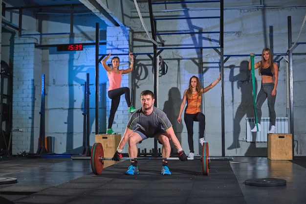 Muskulöser mann, der hocken mit barbell in einer turnhalle tut Premium Fotos