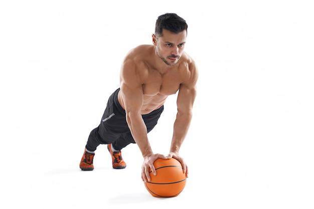 Muskulöser mann, der liegestütze mit basketball tut. Kostenlose Fotos