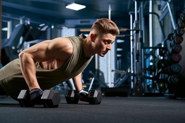 Muskulöser mann, der liegestütze mit hanteln tut. Kostenlose Fotos