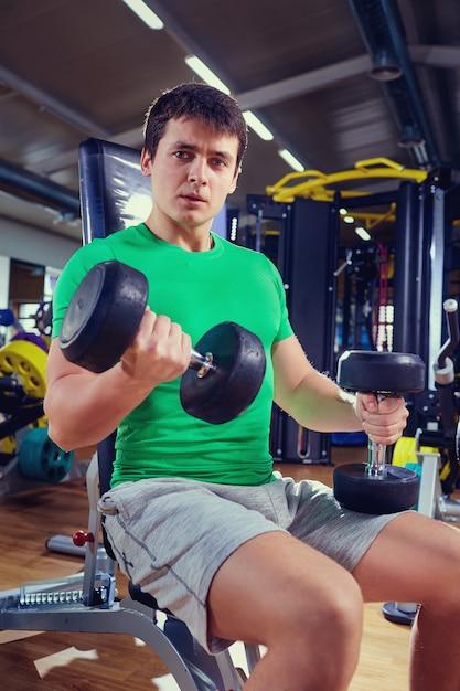 Muskulöser mann in einem grünen t-shirt hebt gewichte der turnhalle an Premium Fotos