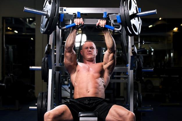 Muskulöser mann in einer turnhalle Kostenlose Fotos