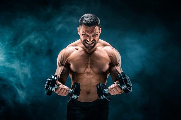 Muskulöser mann mit hanteln Premium Fotos