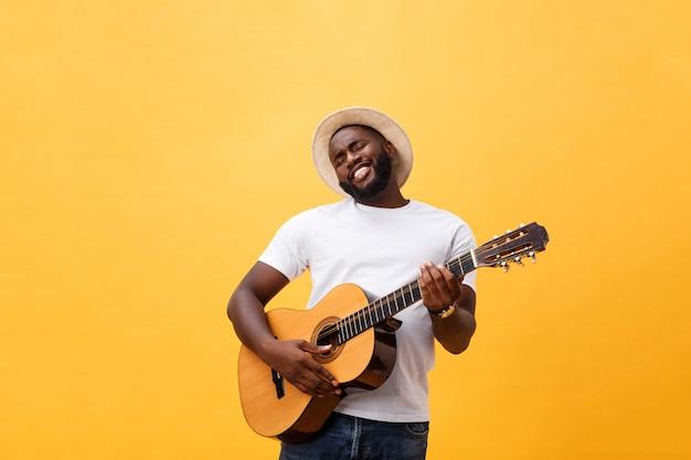 Muskulöser schwarzer mann, der gitarre spielt, jeans und weißes trägershirt trägt. isolieren sie über gelbem hintergrund. Premium Fotos
