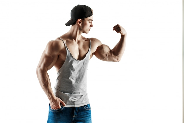 Muskulöser superhoher gutaussehender mann in der baseballmütze und in trägershirt, die auf weißem hintergrund aufwerfen Premium Fotos