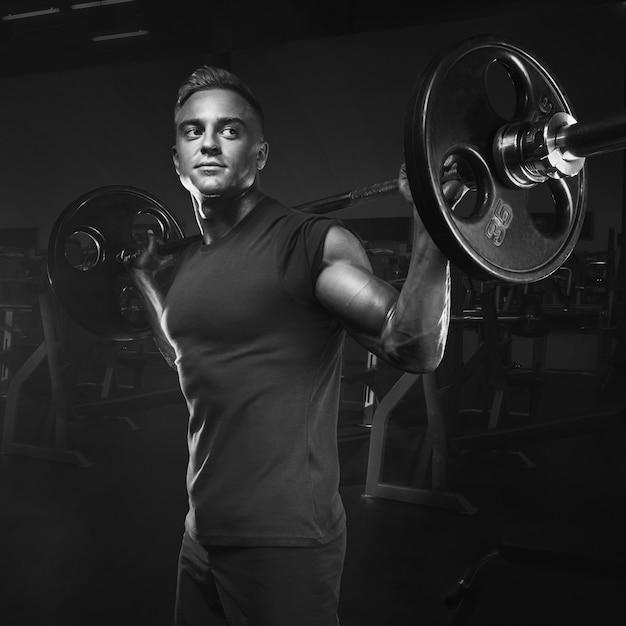 Muskulöses manntraining hockt mit den barbells obenliegend Premium Fotos