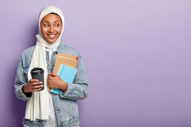 Muslim fröhliche frau mit dunkler haut, schaut weg, trägt weißen schleier, hält kaffee zum mitnehmen Kostenlose Fotos