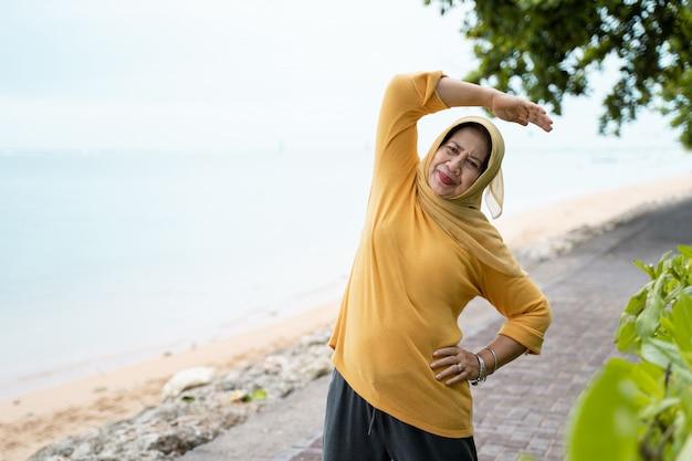 Muslimische ältere frau, die sich im freien ausdehnt und trainiert Premium Fotos