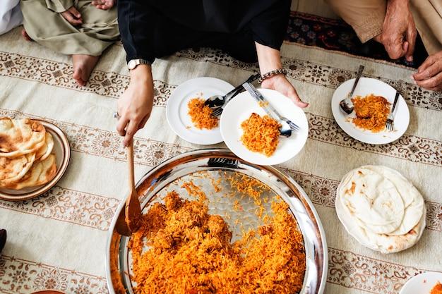 Muslimische familie beim abendessen auf dem boden Kostenlose Fotos