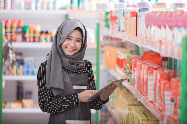 Muslimische frau, die das produkt im laden prüft Premium Fotos