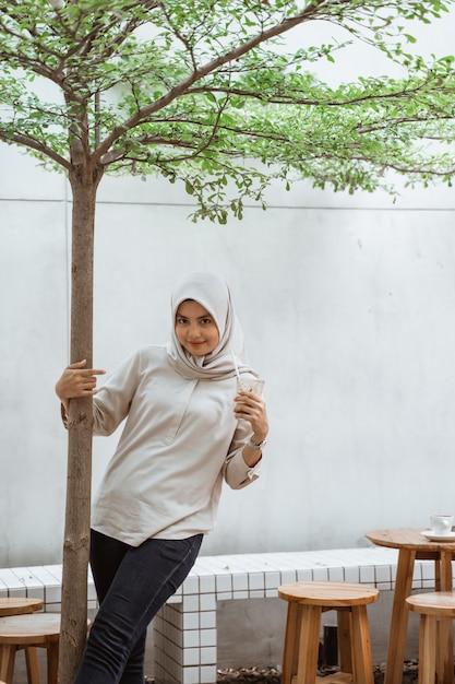 Muslimische frau, die eiskaffee genießt Premium Fotos