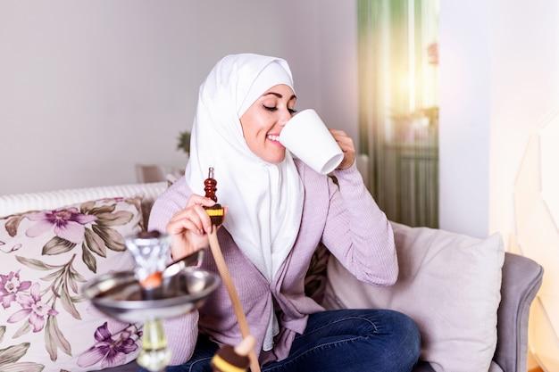 Muslimische frau, die zu hause shisha raucht und kaffee oder tee trinkt. arabisches mädchen raucht shisha Premium Fotos