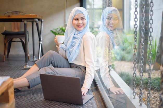 Muslimische frau mit hijab arbeitet mit laptop im café Premium Fotos