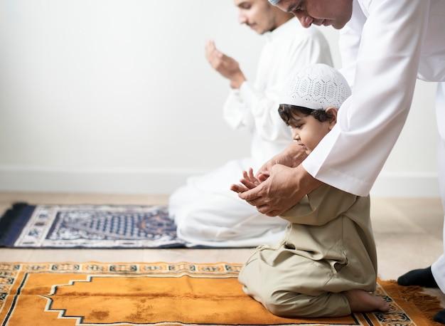 Muslimischer junge, der lernt, dua zu allah zu machen Premium Fotos