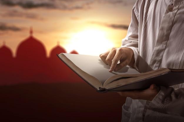 Muslimischer mann, der den koran auf seinen händen liest Premium Fotos